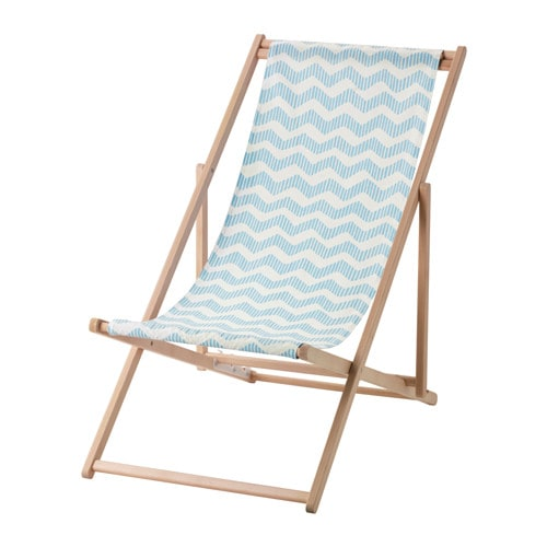 A foldable beach chair in wood with a blue and white patterned fabric seat.
