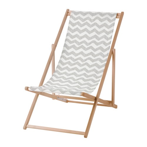 A foldable beach chair in wood with a gray and white patterned fabric seat.
