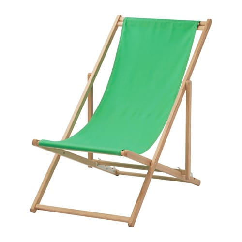 A foldable beach chair in wood with a green fabric seat.