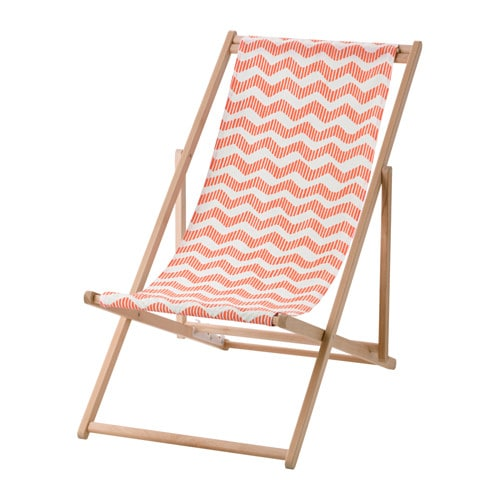 A foldable beach chair in wood with a red and white patterned fabric seat.
