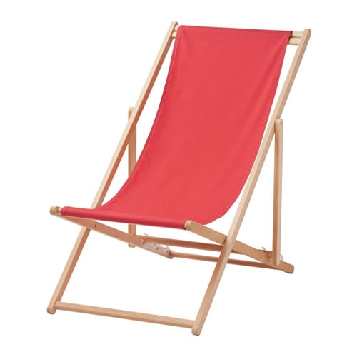 A foldable beach chair in wood with a red fabric seat.