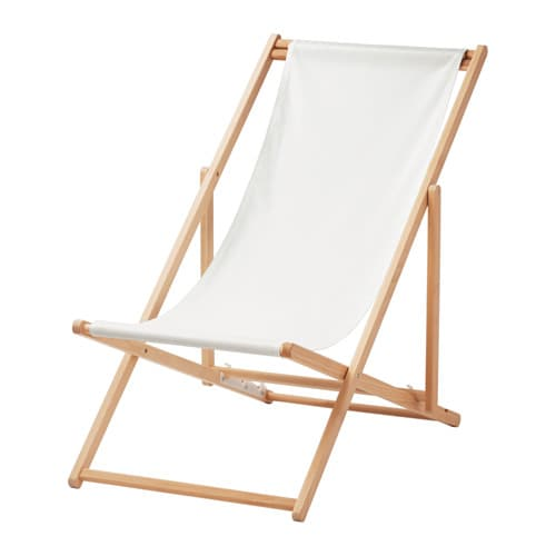 A foldable beach chair in wood with a white fabric seat.