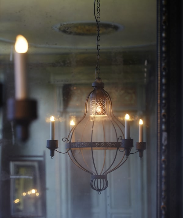 A four-arm chandelier hanging in a cream room, with an ornate door in the background.
