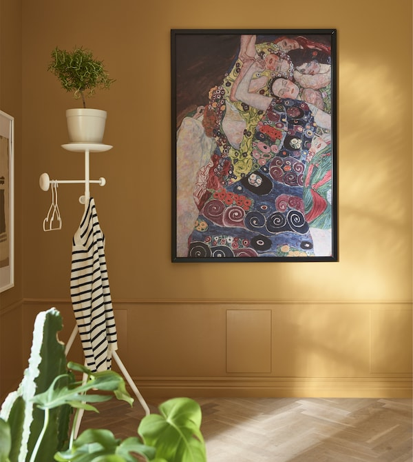 A framed piece of artwork is hung on an ochre wall, with a valet stand in the corner.