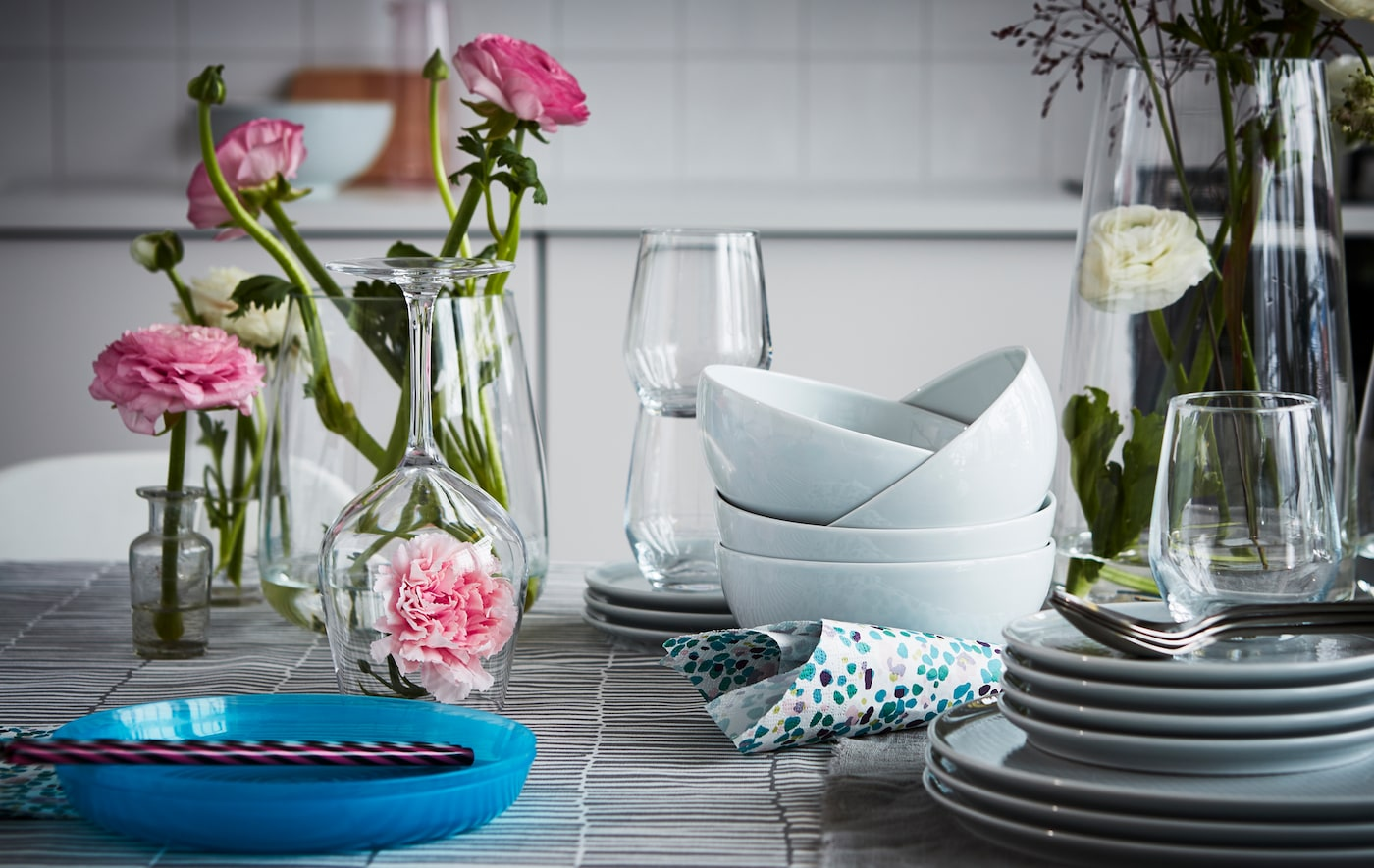 A fresh and flowery table setting with a modern mix of dinnerware, cutlery and beautiful wine glasses.