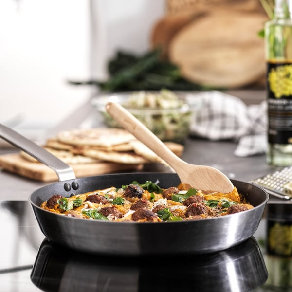 A frying pan on a hob filled with food, with a wooden spoon in it. A bottle of oil and a wooden chopping board is behind it.