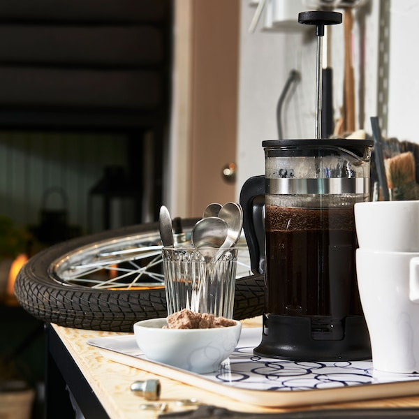 A full coffee press, two cups, and a bowl of biscuits in a garage workspace.
