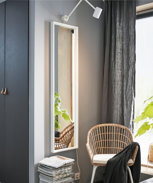 A full-length mirror on a gray wall next to a rattan chair and a pile of magazines.