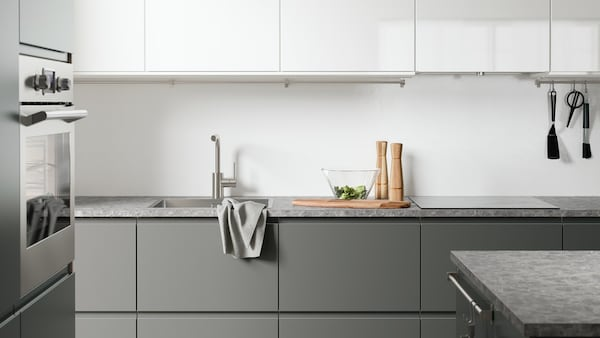 A fully assembled IKEA kitchen with grey base cabinets and white wall cabinets