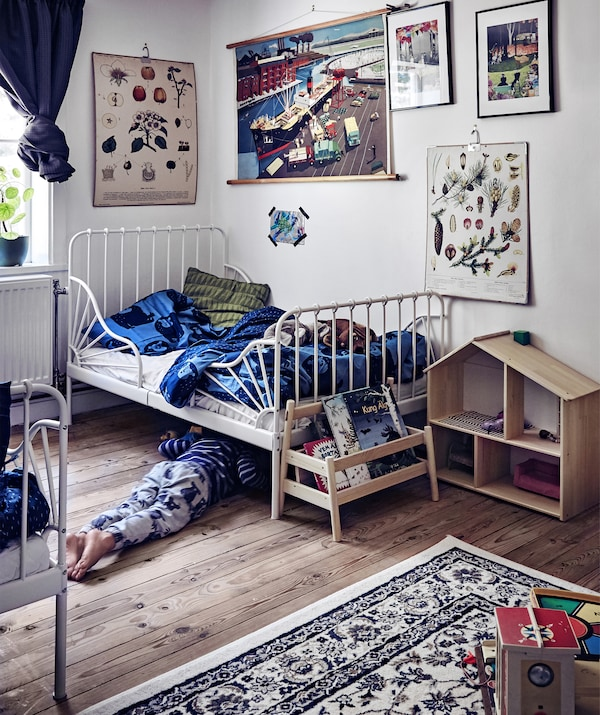 A fun children's bedroom with white walls, book storage, a dolls house and plenty of wall art.