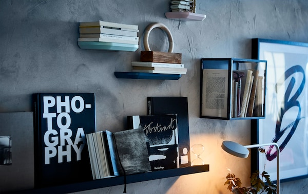 A gallery style wall displaying artworks and books in display cabinets and on picture ledges