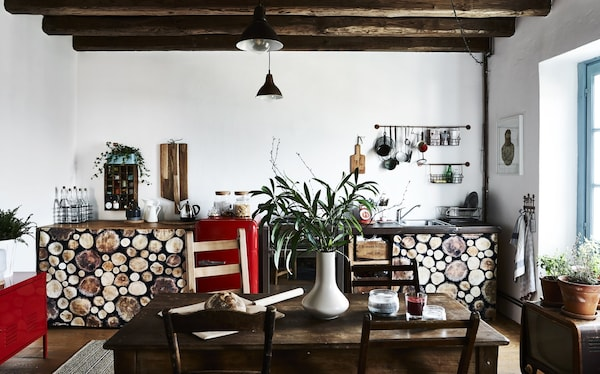 A galley kitchen with aged wood and pops of red.