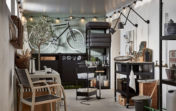A garage-like interior with wall-hung bike, shelving units with outdoor stuff; seating, coffee, mood and functional lighting.
