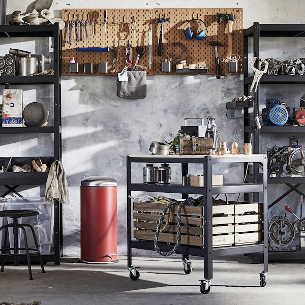 A garage space with a BROR trolley, and various tools on a wall-mounted pegboard.