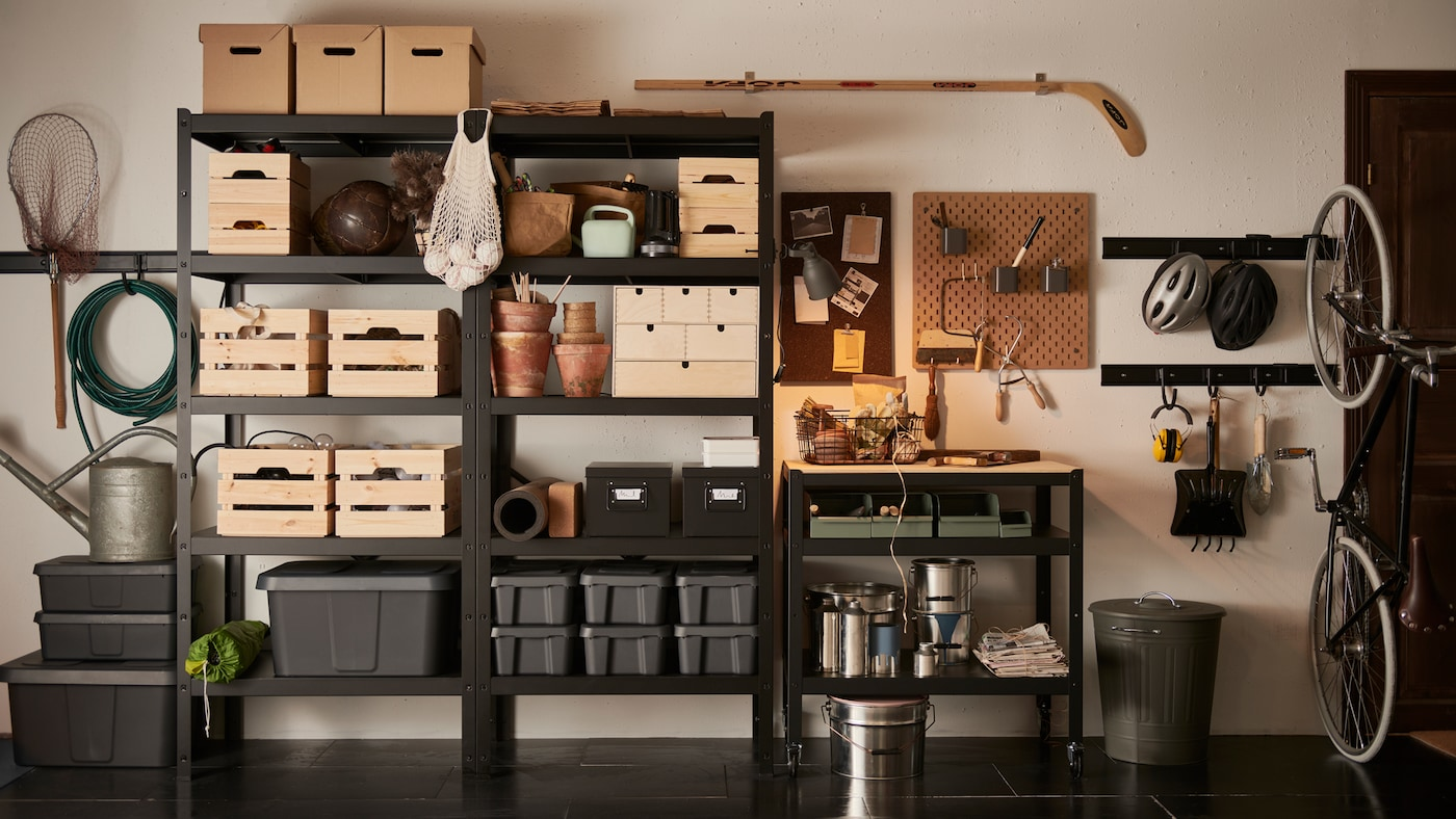 A garage wall with a black BROR shelving unit, filled with wooden, cardboard and plastic boxes in different sizes.