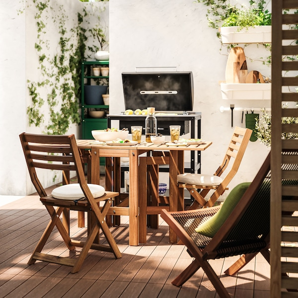 A gateleg acacia table with chairs in an outdoor space, with a barbecue in the background.