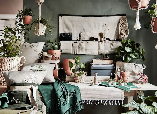 A gathering of BOTANISK products including baskets, textiles, plant pots, and hanging pouches in a room.