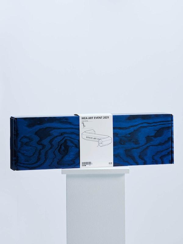 A Gelchop kreatív csoport által az IKEA ART EVENT 2021 kollekcióhoz tervezett imbuszkulcs alakú LED-es asztali lámpát magába foglaló kék doboz, fehér talapzaton