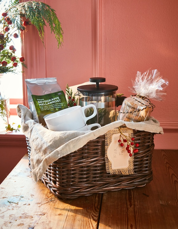 A gift basket with a bag of coffee, a coffee maker, mugs and oat biscuits.
