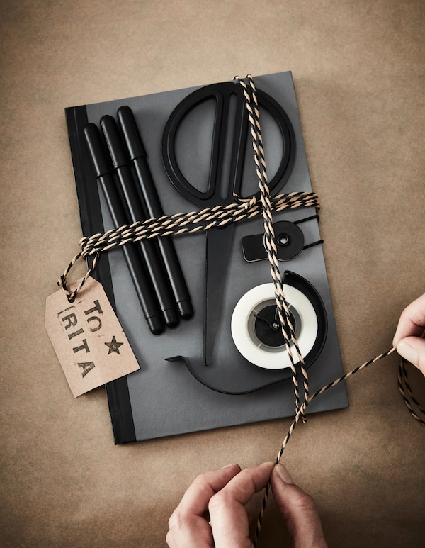 A gift for creativity with a note-book, pens, scissors and tape.