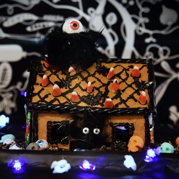 A gingerbread house decorated with candy corn, black licorice, black frosting, and other halloween decorations.