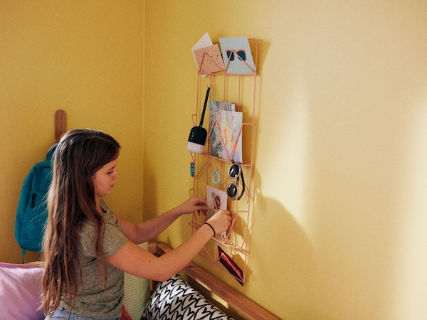 A girl arranging pictures into a wire storage rack in a bedroom with a yellow wall.