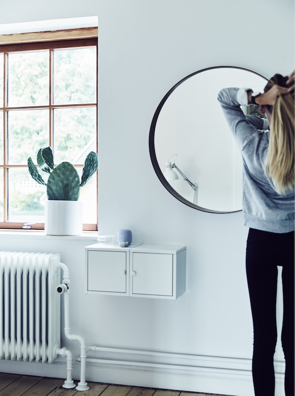 A girl doing her hair in the mirror.