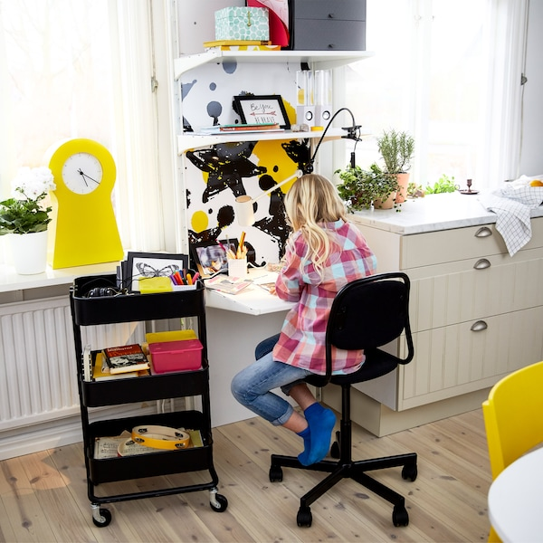 A girl doing her homework at a small desk top mounted on the wall and above the desk several shelves storing boxes.