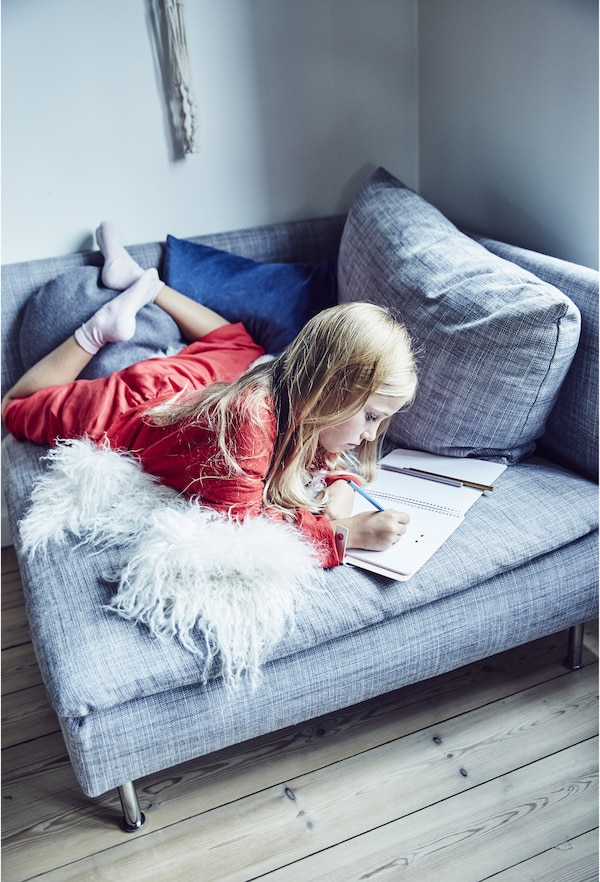 A girl doing homework on a chair.