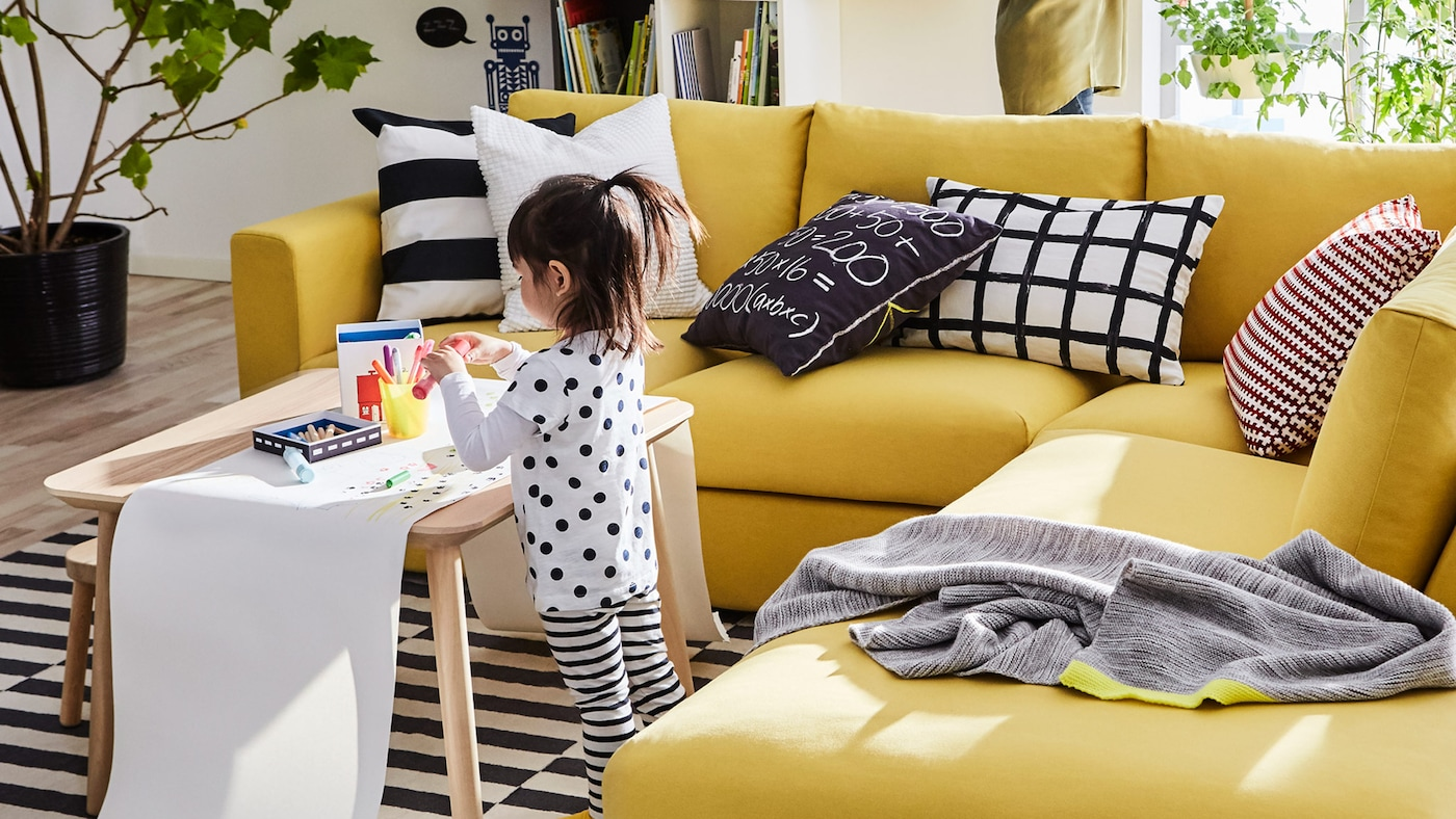 A girl drawing won a long roll of paper on top of a coffee table and next to a yellow IKEA VIMLE three-seat sofa sectional.