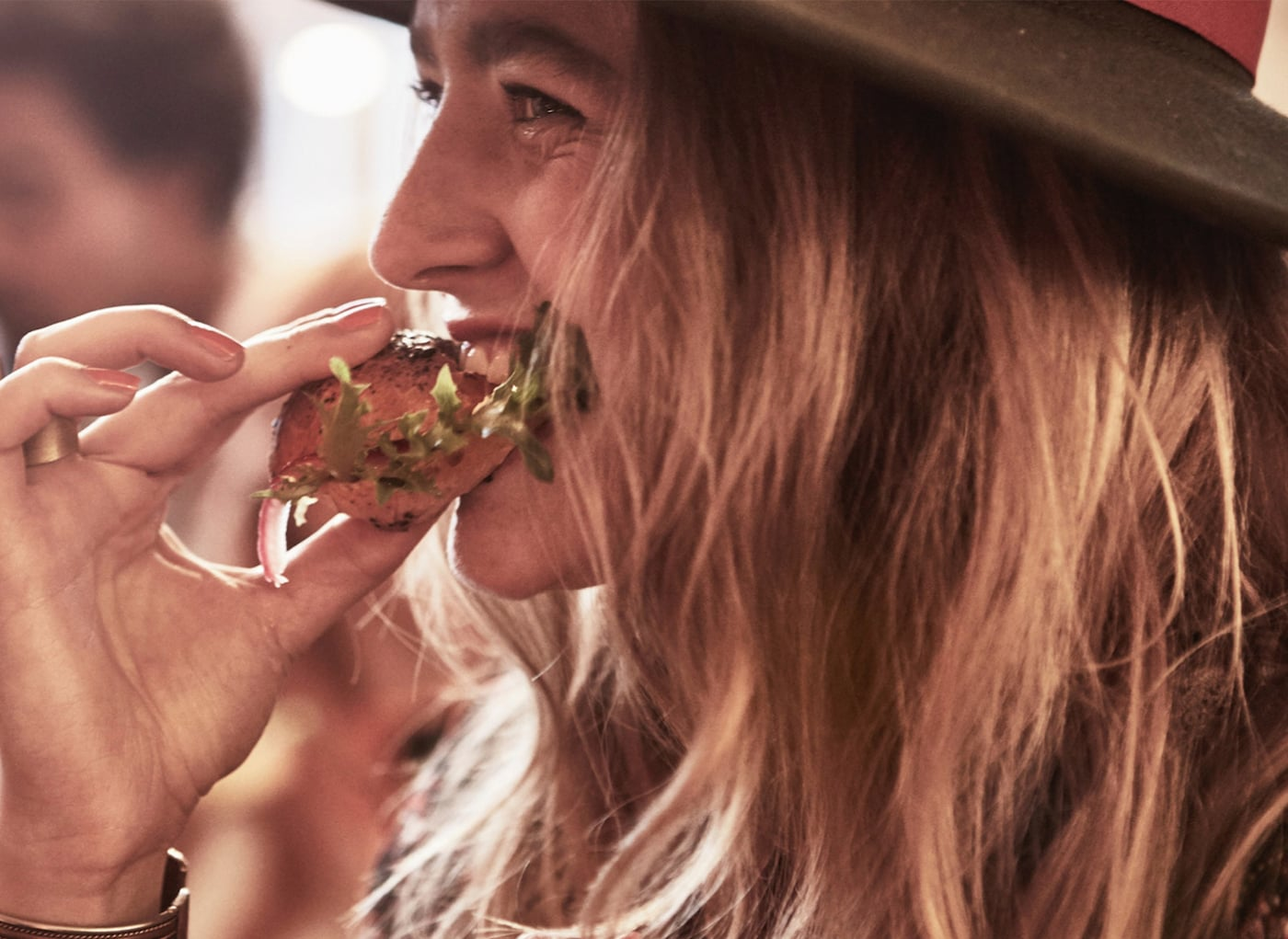 A girl eating a snack with bread and salad in it.