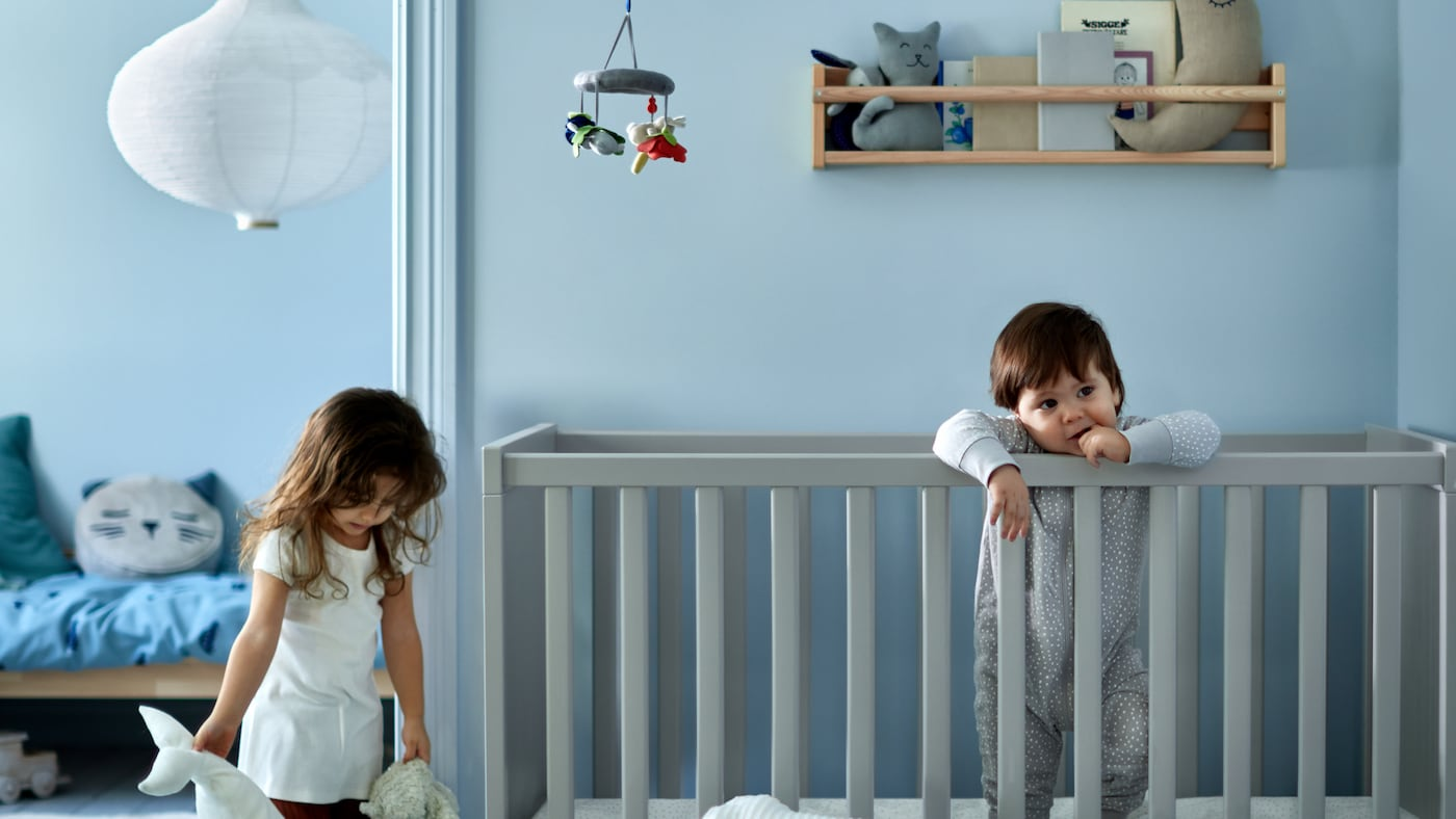 A girl holding two soft toys beside a toddler standing in a grey cot, with a children's bed with blue bed linen behind.