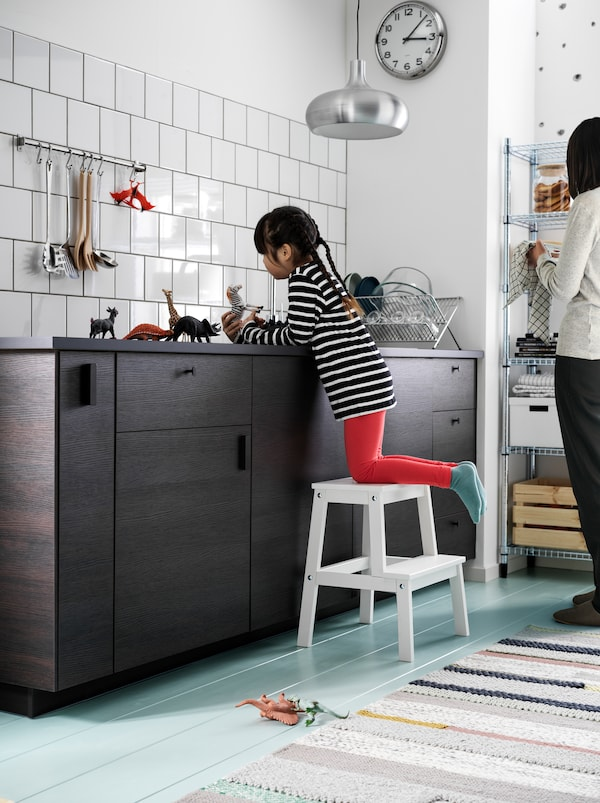 A girl, perched on a BEKVÄM step stool, plays with small toy animals on a dark kitchen worktop. A woman stands nearby.