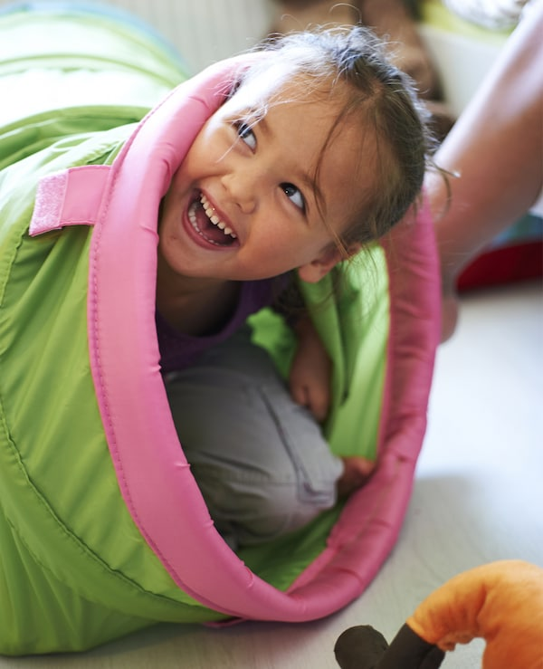 A girl playing in a green and pink IKEA toy tunnel.