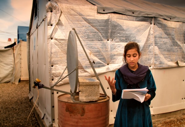 A girl reading from a book in front of a makeshift satellite and temporary buildings.