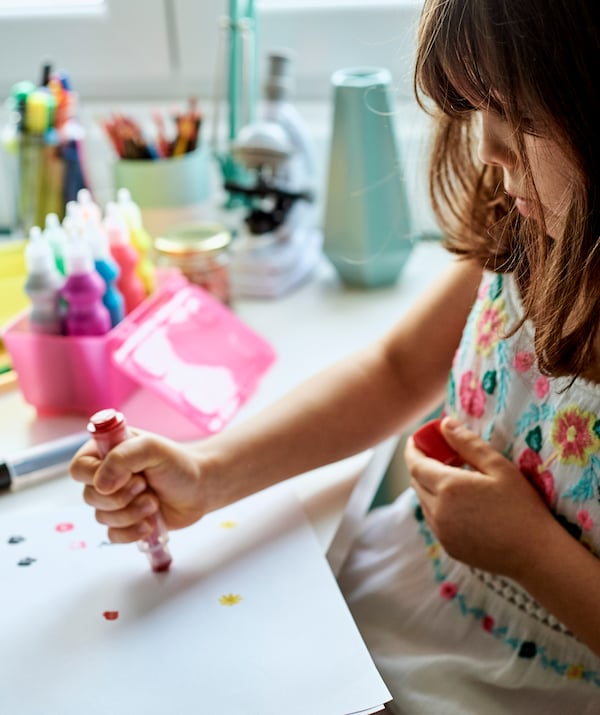 A girl sits at a desk using a red stamp pen to make patterns on paper, there are tubes of paints in a pink tub beside her.