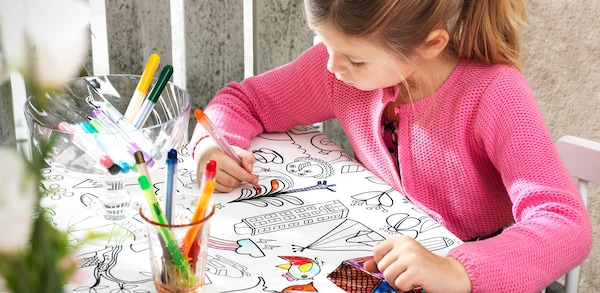a girl sitting by the table coloring