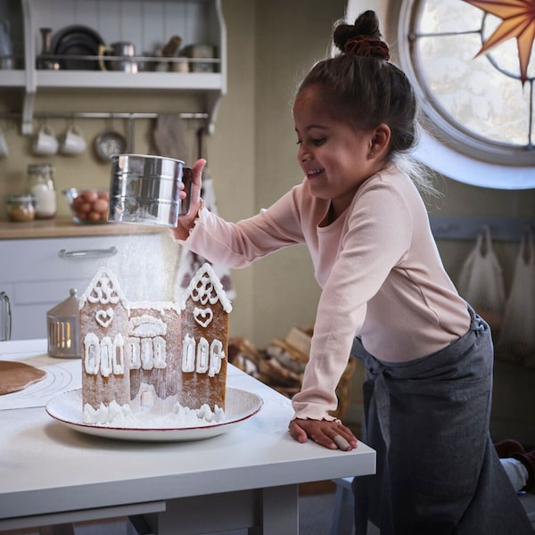 A girl uses an IDEALISK flour sifter to sprinkle sugar like a snowstorm on top of an iced gingerbread house.