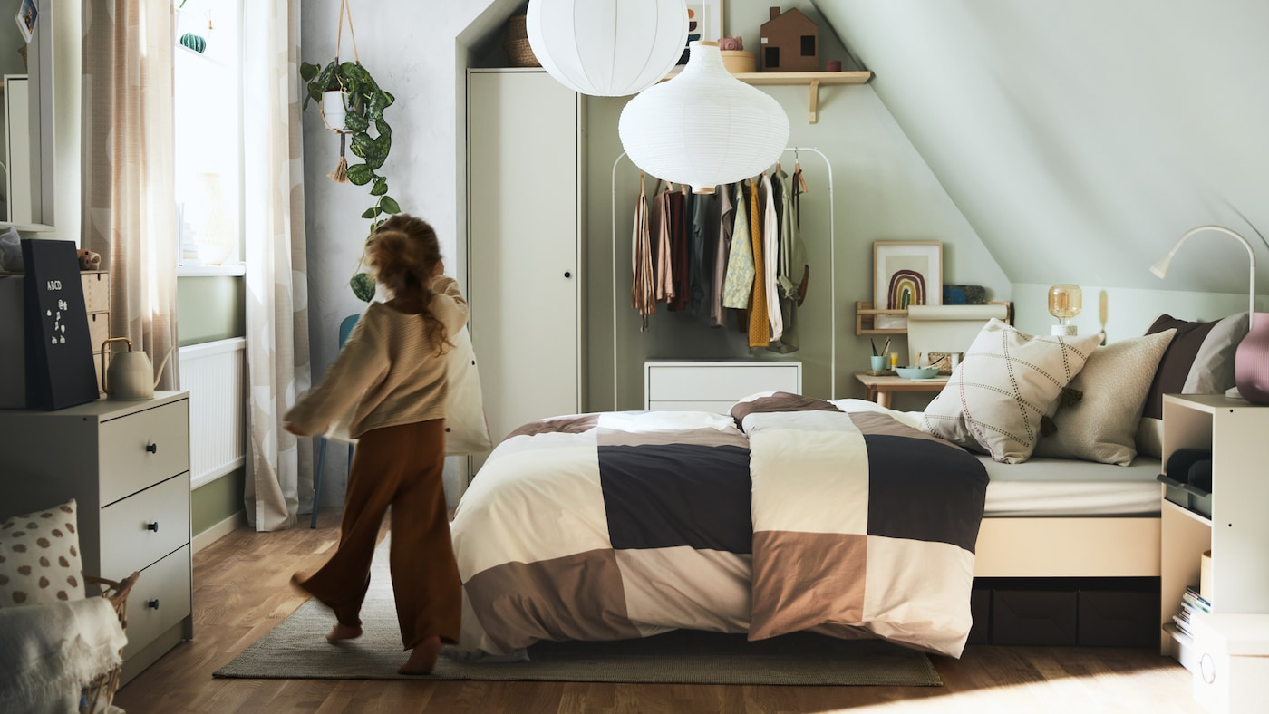 A girl walking into a bedroom with a bed made with brown/grey checkered bed linen, plus various storage and white pendants.