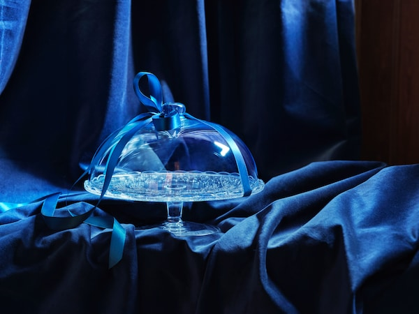 A glass cakestand, wrapped in a bow on a blue velvet background