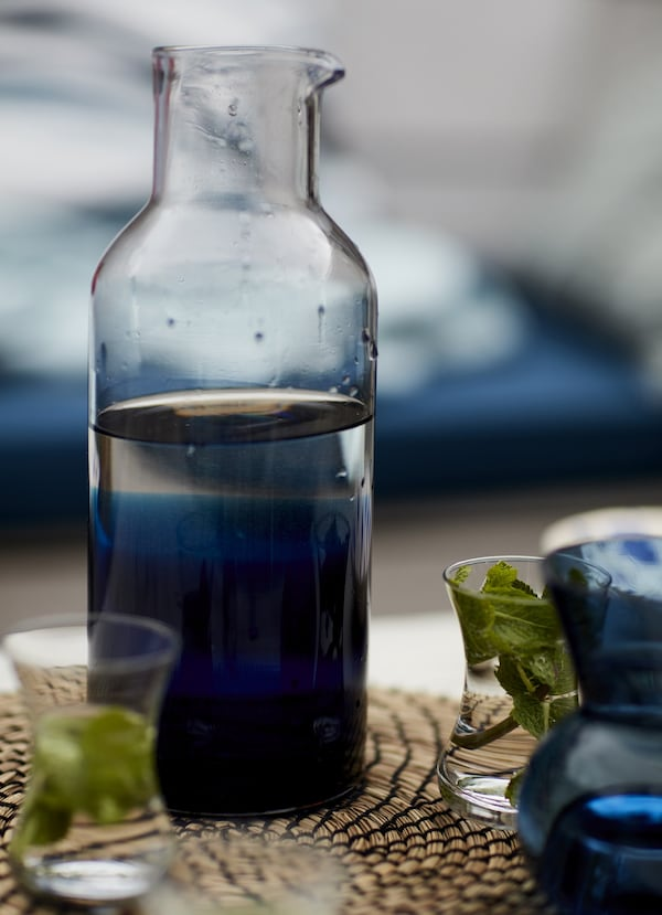 A glass carafe on a woven place mat.