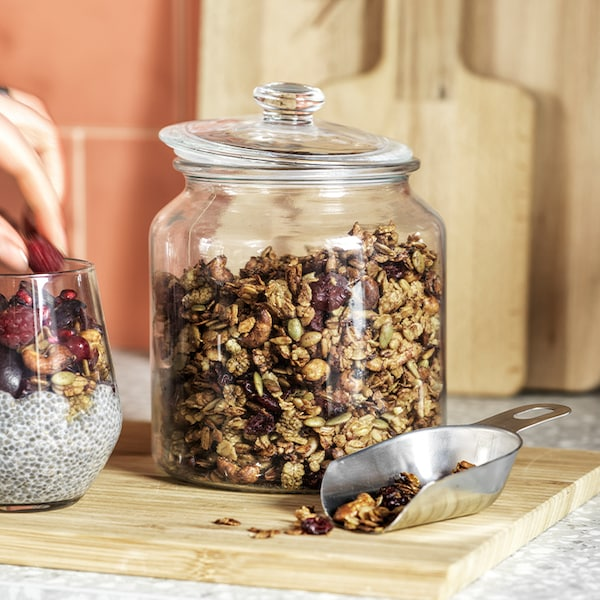 A glass jar with granola inside is placed on a wood chopping board with a metal scoop to the side.