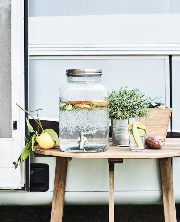 A glass jar with tap and lemons on a wooden table.