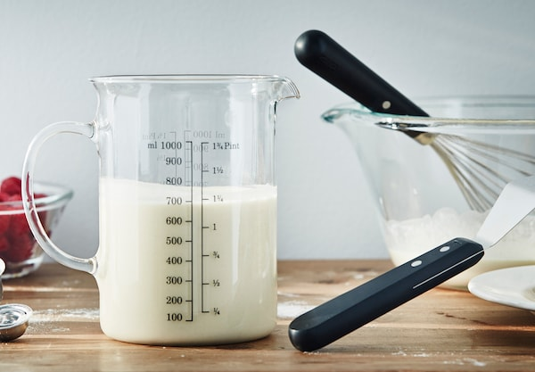 A glass jug with milk beside a glass bowl with kitchen implements.