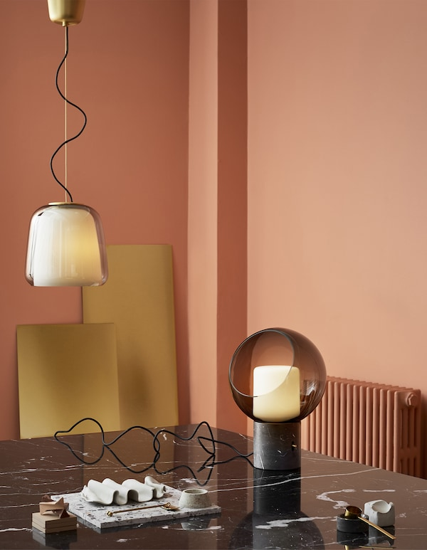 A glass pendant lamp and globe table lamp in a pink room with black marble table.