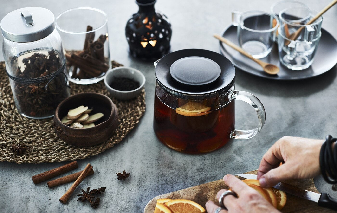 A glass pot of tea and jars of seasonal spices and fruits, on a worktop.
