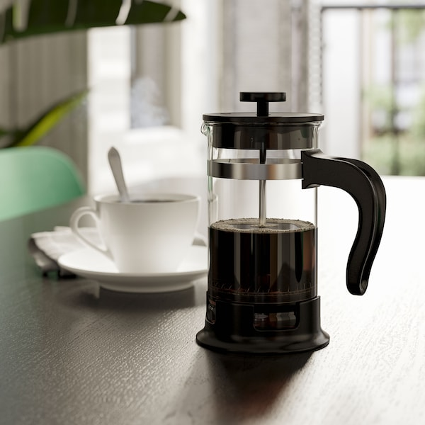 A glass/stainless steel UPPHETTA french press coffee maker on a table with a white cup.