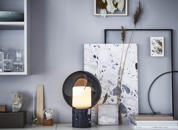 A glass table lamp, ornaments and artwork on a surface.