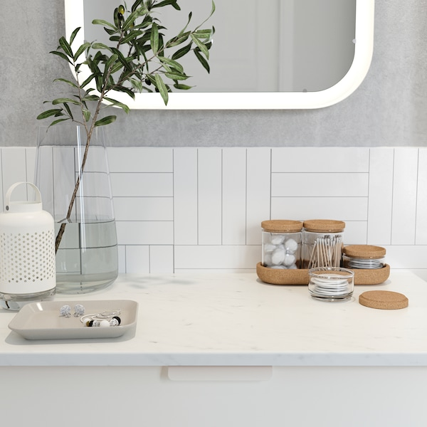 A glass vase, a bowl with jewellery and cotton swabs in a glass jar with cork lid stand on a countertop with marble effect.