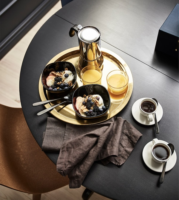 A GLATTIS round tray in brass-coloured, metallised stainless steel holds breakfast on a table in the bedroom.